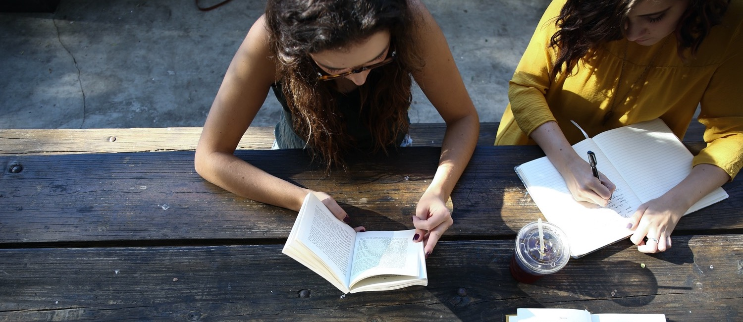 Students reading books at a picnic table